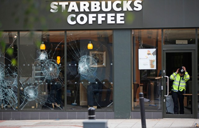A policeman comes out of Starbucks cafe in the area of Clapham in the aftermath left by riots in London Tuesday, August 9, 2011.
